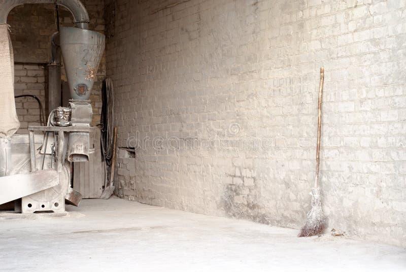 Elektrycznej kukurudzy młyńska i drewniana miotła przy ścianą zdjęcia royalty free