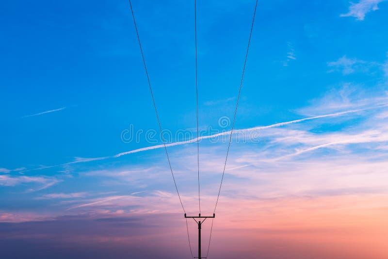 Elektrycznej podstacji oszczędnościowy słup, stan i wysoka woltaż linii energetycznej sylwetka z błękitnym chmurnym niebem przy z fotografia royalty free