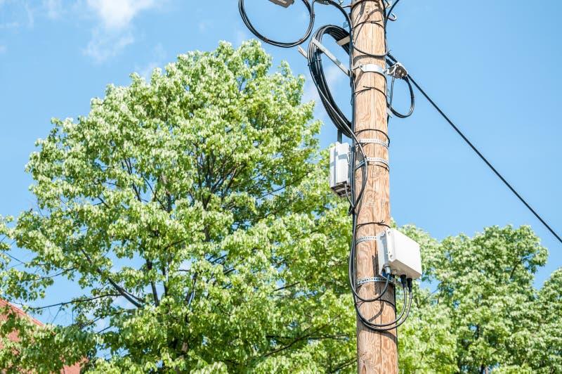 Elektryczni druty na drewnianym ulicznym słupie z komunikacyjnymi pudełkami i niebieskiego nieba tłem interneta lub telefonu komó zdjęcie royalty free