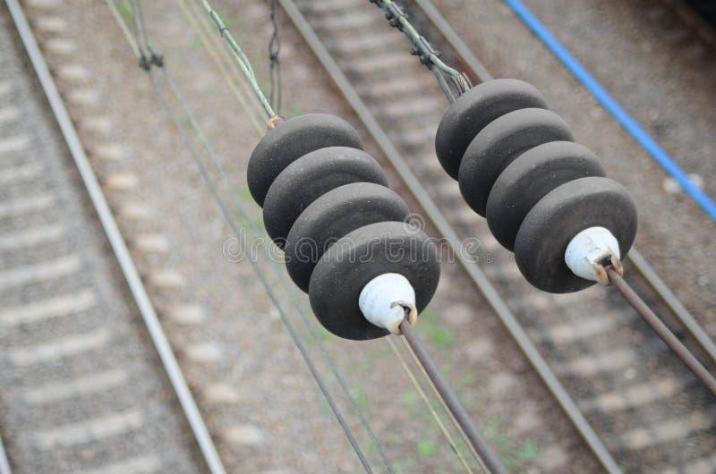 Elektryczni izolatory na kontaktowych drutach na tle zamazany kolejowy ślad Makro- fotografia z selekcyjnym focu fotografia stock
