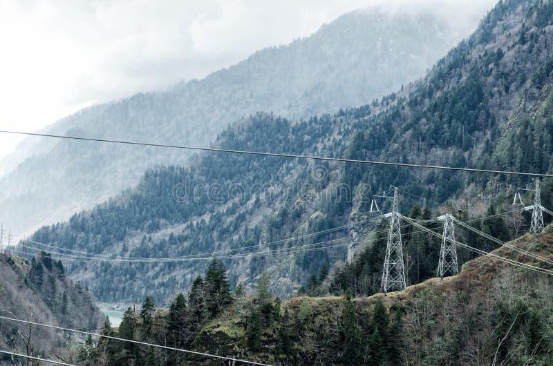 Elektryczni słupy w górach, elektryczność w halnych regionach, skomplikowana elektryfikacja uwarunkowywać obrazy stock
