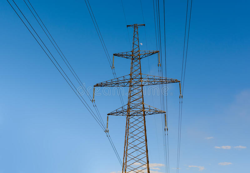 Elektryczność pilon sylwetkowy przeciw niebieskiego nieba tłu Woltażu wysoki wierza fotografia stock