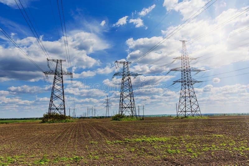 Elektryczność pilony iść w odległość nad lato wsią obrazy stock