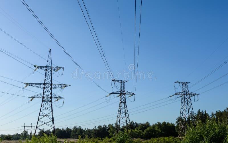 Elektryczność pilony iść w odległość nad lato wsią fotografia royalty free
