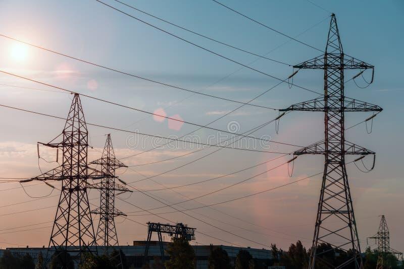 Elektryczność przekazu pilon sylwetkowy przeciw niebieskiemu niebu przy półmrokiem zdjęcie stock