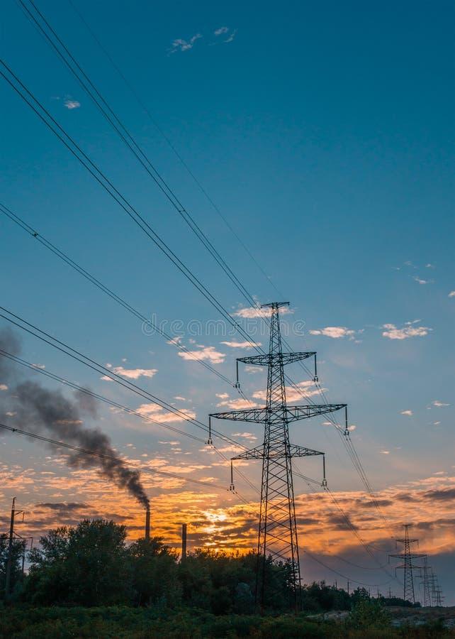Elektryczność przekazu pilon sylwetkowy przeciw niebieskiemu niebu przy półmrokiem obraz stock