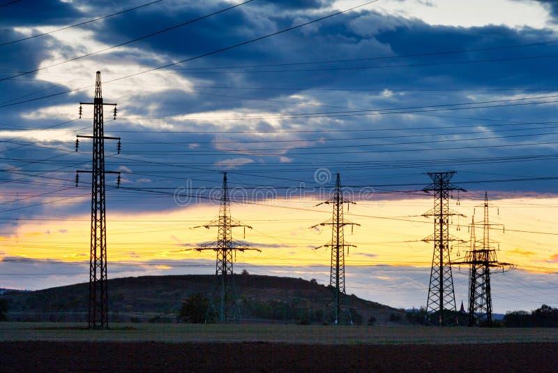 Elektryczność - władza przemysł energetyczny - Elektryczni słupy przy słońcami zdjęcie royalty free