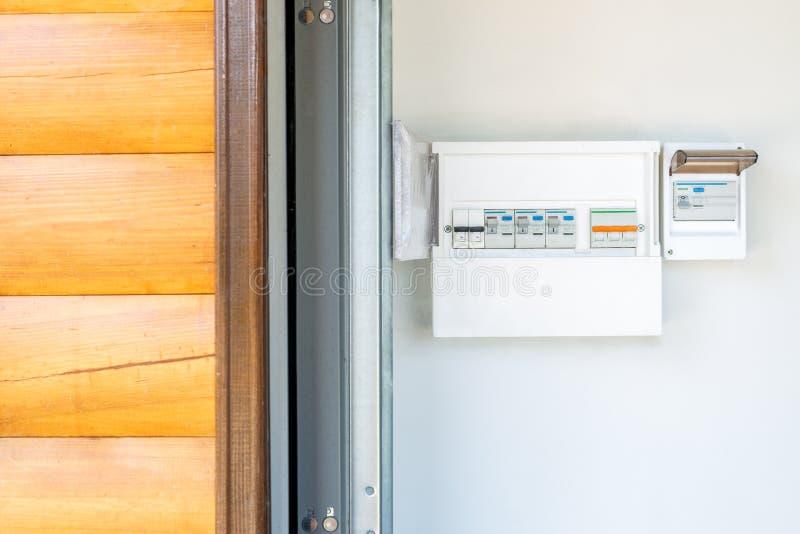 Elektryczności dystrybucji deska z setem automatyczni obwodów łamacze, zmiany blisko wejściowego drzwi drewniany garażu budynek i fotografia stock