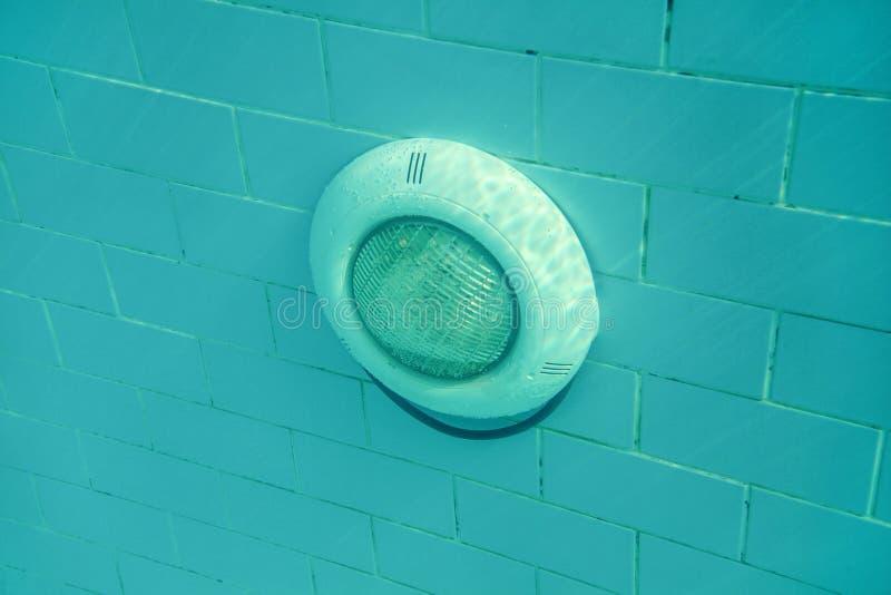 Elektryczny światło w basenie na błękitnych płytkach ściany, słońce błyszczy z góry Podwodna fotografia obrazy stock