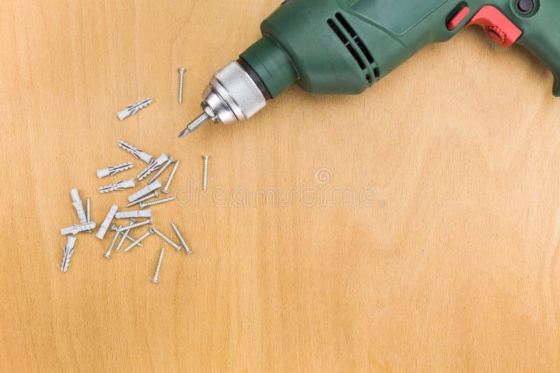 Elektryczny świder i śruby na drewnianej podłoga fotografia stock