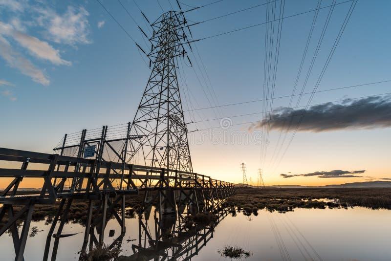 Elektryczny góruje z prowadzić linie przy zmierzchem, z odbiciami w wodzie zdjęcie royalty free