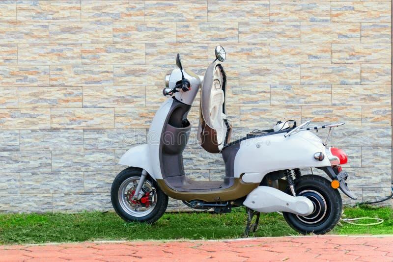 Elektryczny moped parkujący blisko ściany dla ładować Hulajnoga - zielony transport zdjęcie stock