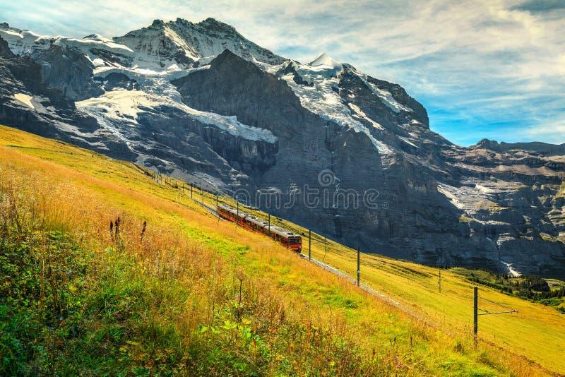 Elektryczny turysty pociąg z wysokimi górami, Bernese Oberland, Szwajcaria, Europa zdjęcie royalty free
