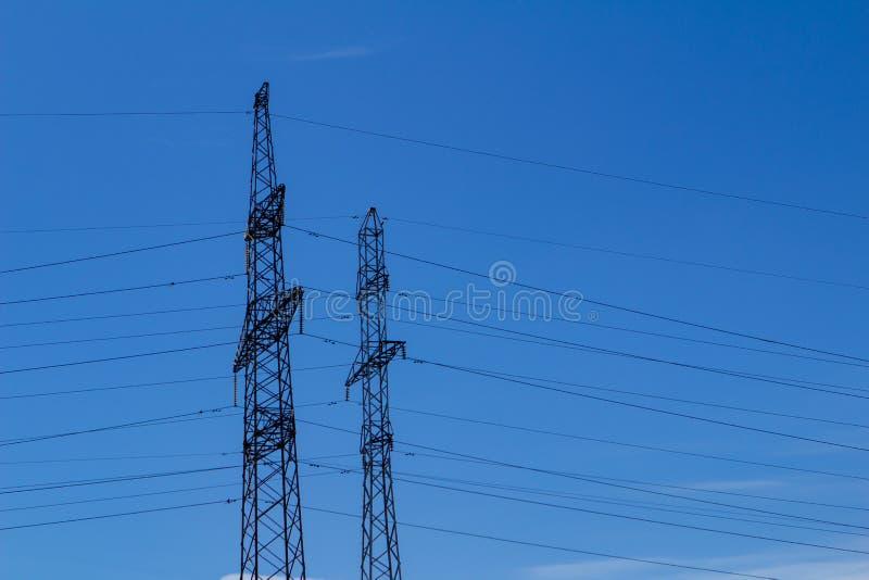 Elektryczny wysoki woltażu wierza z elektryczną linią przeciw chmury niebieskiemu niebu zdjęcie royalty free