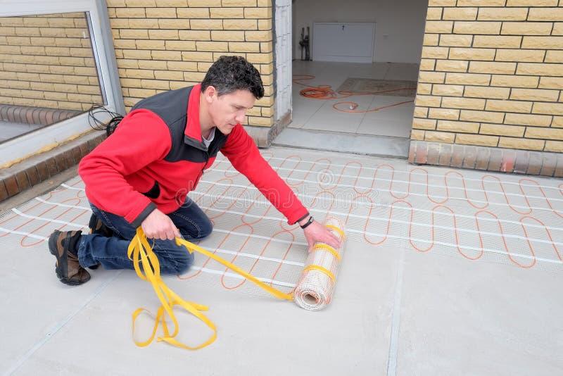 Elektryk instaluje grzejnego elektrycznego kabel na betonowej podłodze Mężczyzna usuwa adgesive taśmy zdjęcie stock