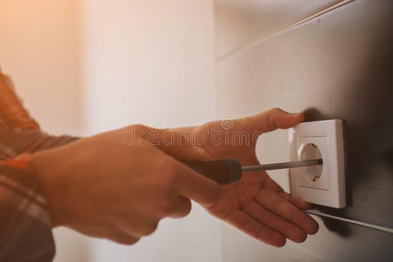 Elektryk, elektryk instaluje nową aktualną nasadkę z śrubokrętem Instalujący elektrycznego ujście lub nasadkę - obraz royalty free
