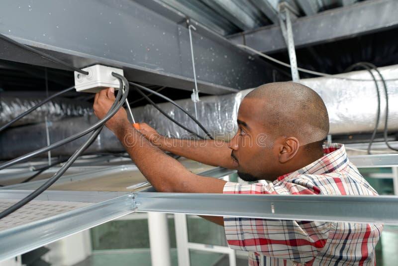 Elektryk pracujący w podsufitowym panelu zdjęcia stock