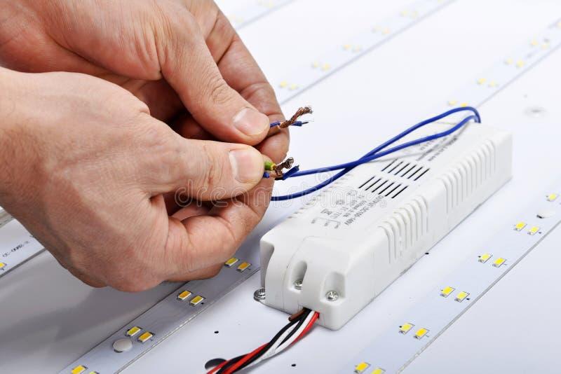 Elektryk ręki łączą druty dowodzona lampa zdjęcie stock