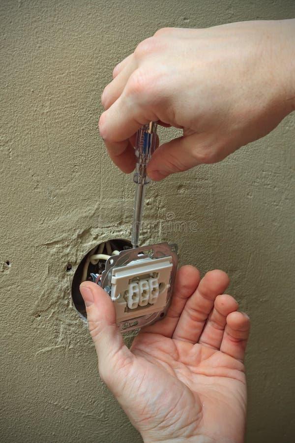 Elektryk ręki z śrubokrętem instaluje lekką zmianę w ścianie obraz royalty free