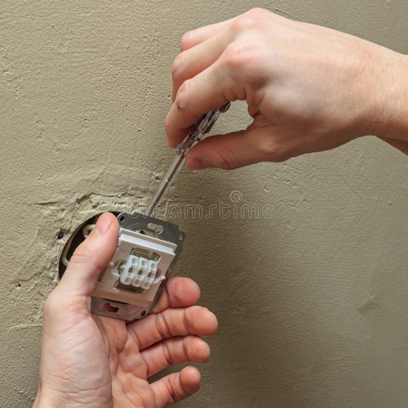 Elektryk ręki z śrubokrętem instaluje lekką zmianę w ścianie zdjęcie stock
