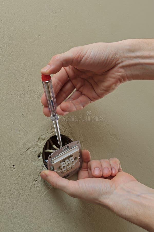 Elektryk ręki z śrubokrętem instaluje lekką zmianę w ścianie zdjęcie royalty free