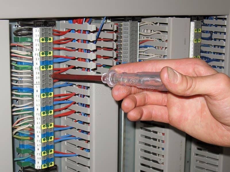 Elektryk używa śrubokrętu woltażu wskaźnika patrzeć dla wadliwych działań w elektrycznym panelu obrazy stock