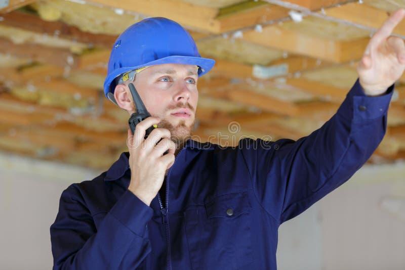 Elektryk używa walkie talkie komunikować z drużyną zdjęcie stock