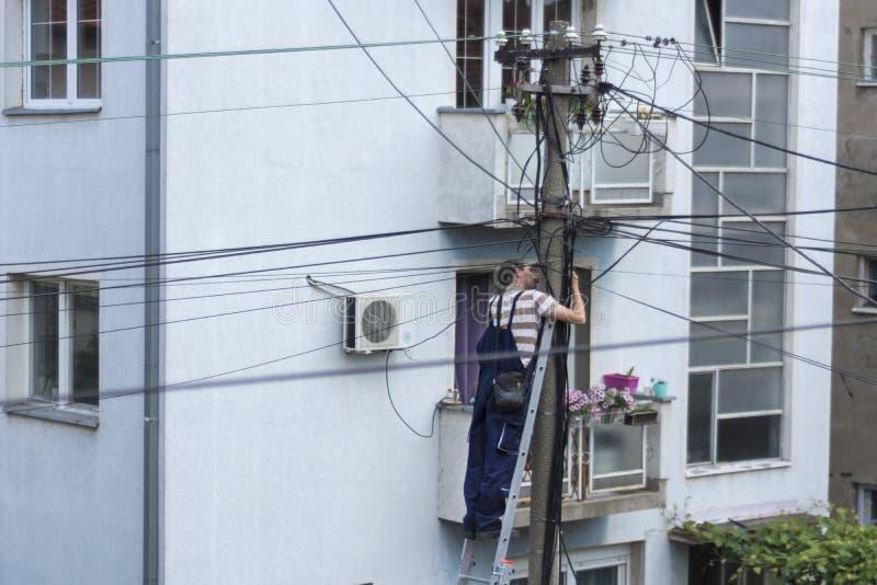 Elektryka pracownik na drabiny naprawy instalaci elektrycznej na elektryczność filarze lub Oszczędnościowym słupie zdjęcia stock