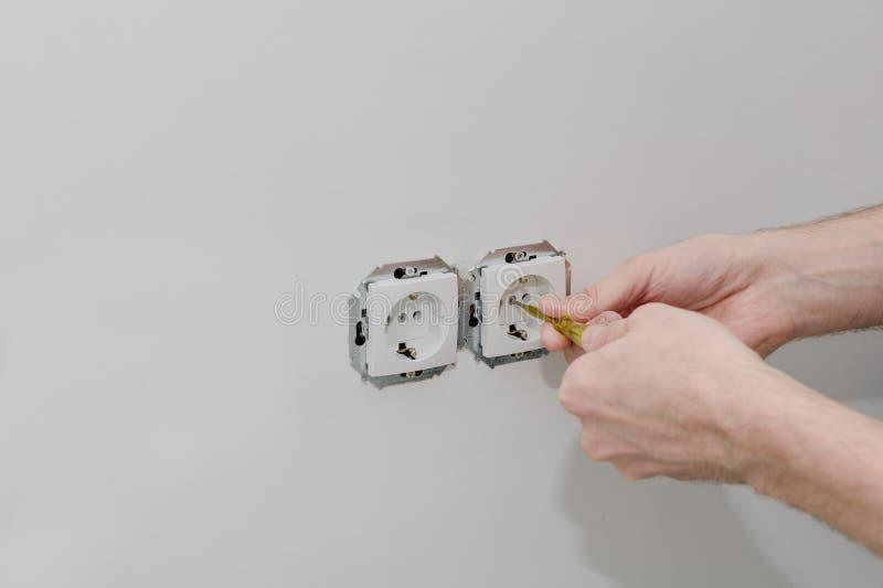 Elektryka ` s ręki są instalującym nasadką zdjęcie royalty free