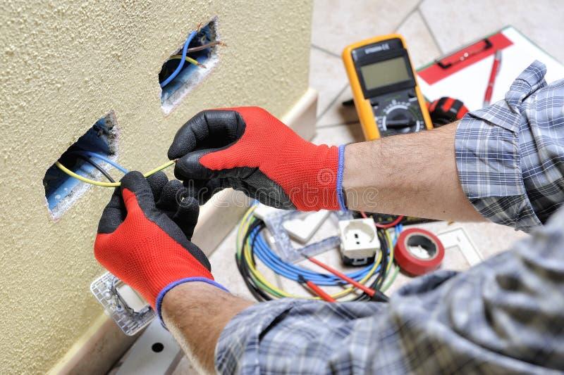 Elektryka technik przy pracą z zbawczym wyposażeniem na mieszkaniowej instalaci elektrycznej obrazy royalty free