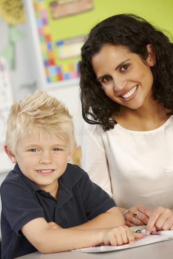 Elementär ålderskolpojkeläsebok i grupp med läraren royaltyfria foton