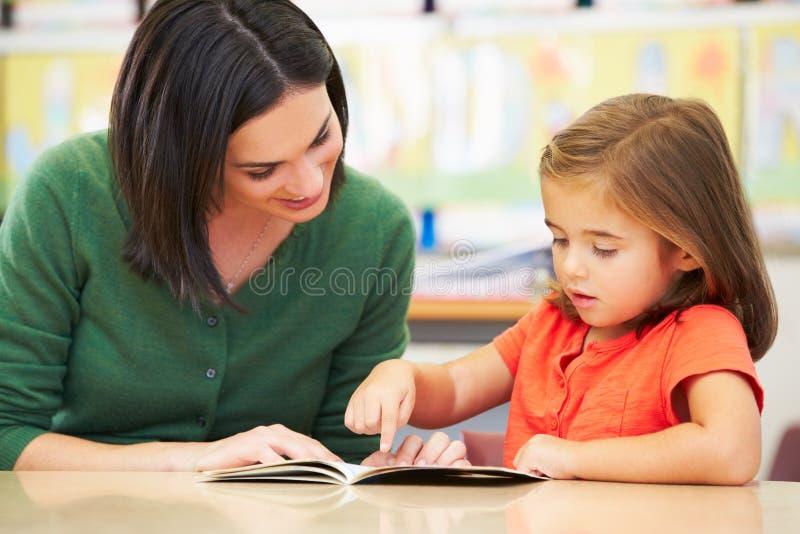 Elementär elevläsning med läraren In Classroom royaltyfria bilder