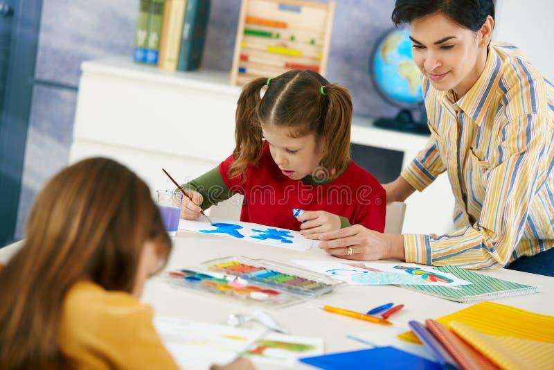 Barn som målar i konst, klassificerar på grundskolan royaltyfri bild