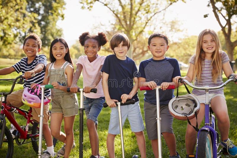 Elementära ålderskolaungar på cyklar och sparkcyklar i en parkera royaltyfri fotografi