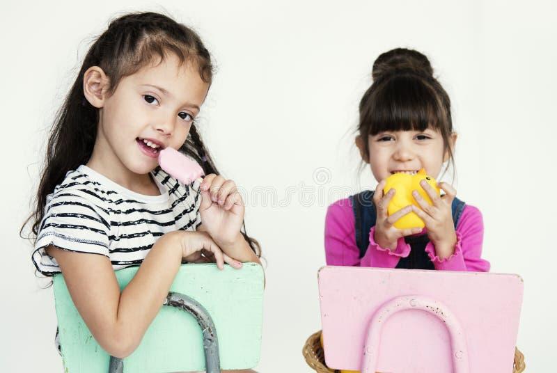 Elementära ålderskolflickor som sitter på stolen på vitBacen royaltyfria bilder