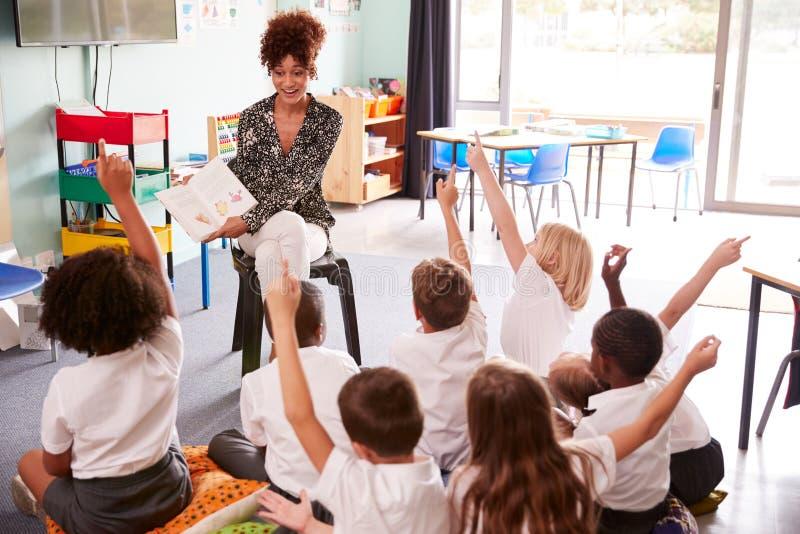 Elementära elever som bär enhetliga lönelyfthänder för att svara fråga som lärarinnan Reads Book royaltyfria foton
