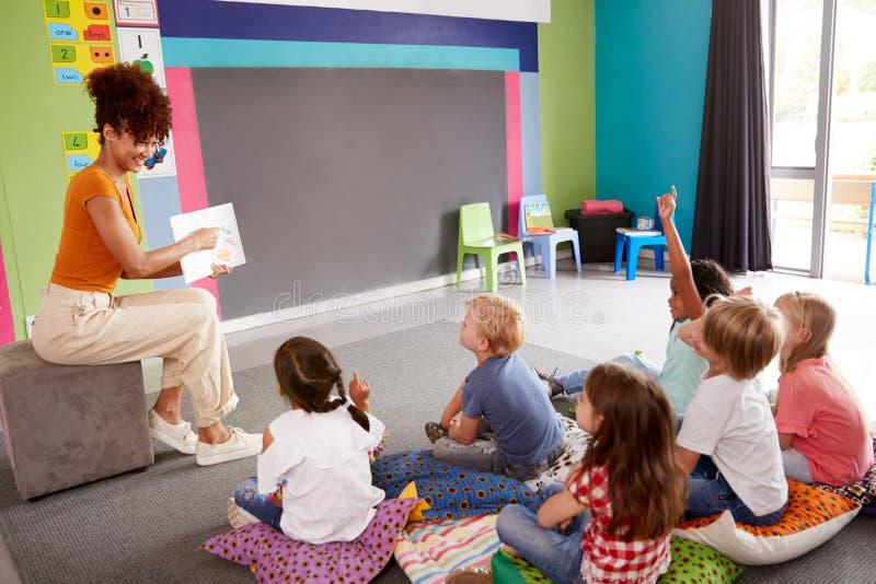 Elementära elever som lyfter händer för att svara fråga som det lärarinnaReads Story In klassrumet arkivfoto