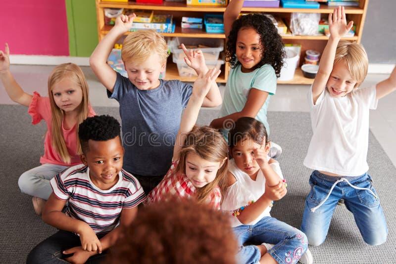 Elementära elever som lyfter händer för att svara fråga som det lärarinnaReads Story In klassrumet royaltyfria bilder
