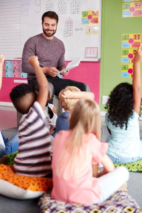 Elementära elever som lyfter händer för att svara fråga som det Reads Story In för manlig lärare klassrumet arkivfoton