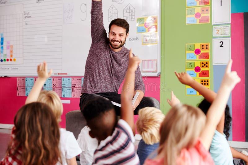 Elementära elever som lyfter händer för att svara fråga som det Reads Story In för manlig lärare klassrumet fotografering för bildbyråer