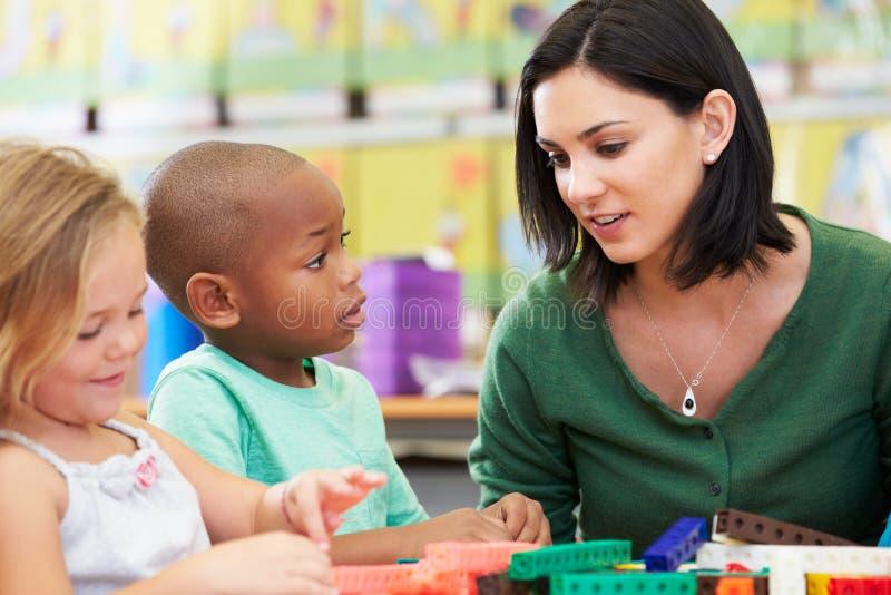 Elementära elever som räknar med läraren In Classroom royaltyfria bilder