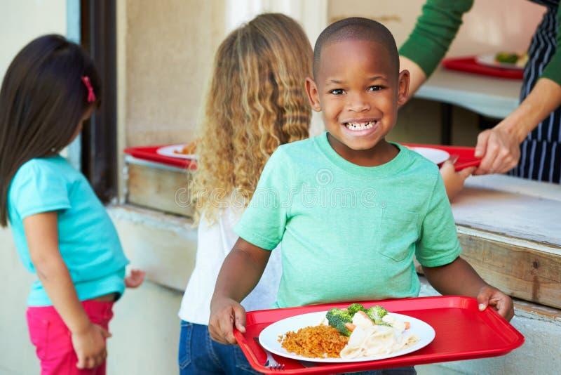 Elementära elever som samlar sund lunch i kafeteria royaltyfri foto