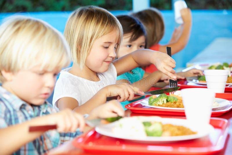 Elementära elever som tycker om sund lunch i kafeteria royaltyfri bild