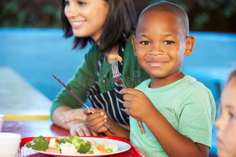 Elementära elever som tycker om sund lunch i kafeteria arkivfoton