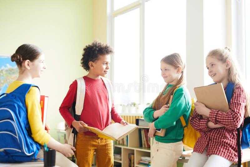 Elementära studenter som diskuterar skolaprojekt arkivfoton