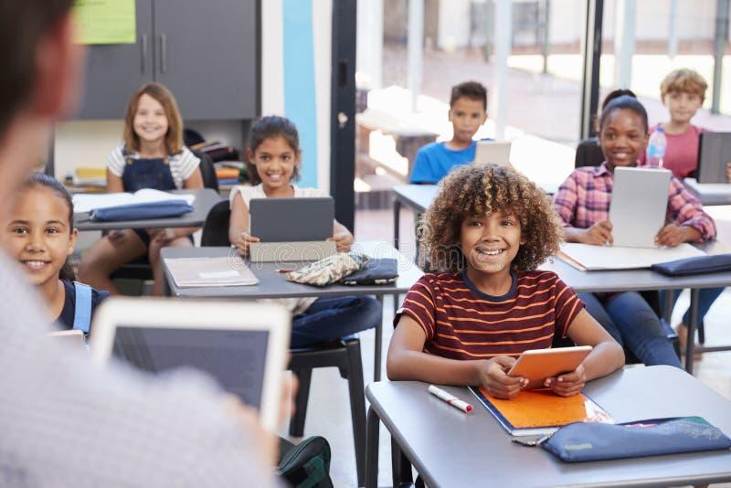 Elementära studenter som ser läraren, över skuldrasikt royaltyfria foton