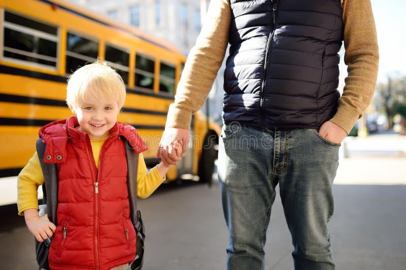 Elementära studenthållhänder hans fader nära den gula skolbussen på bakgrund arkivbilder