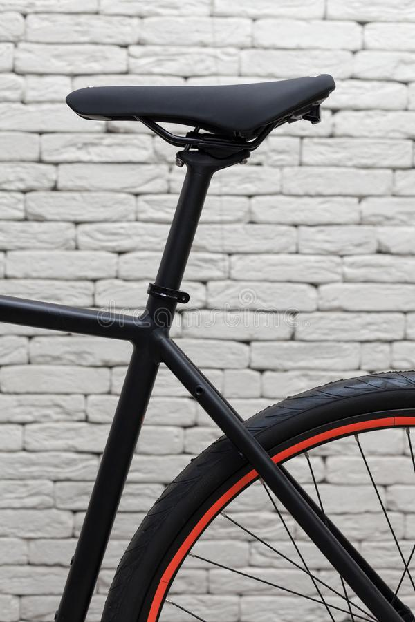 Element of a bicycle. Black saddle against a white brick wall. stock image