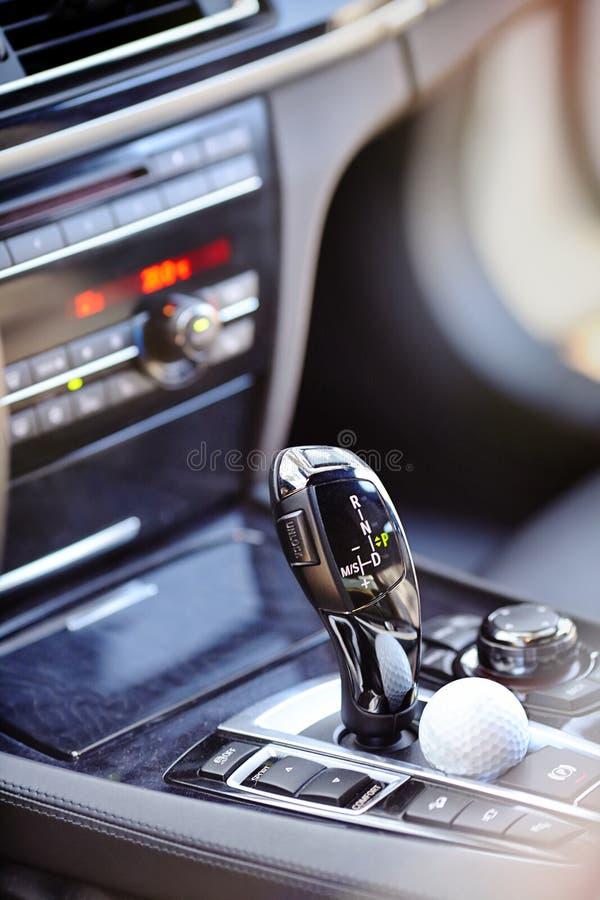 Element des Innenautomatikgetriebeschalthebels des modernen Luxusautos mit Modusknöpfen mit dem Golfball, der nahe bei ihm liegt stockfoto