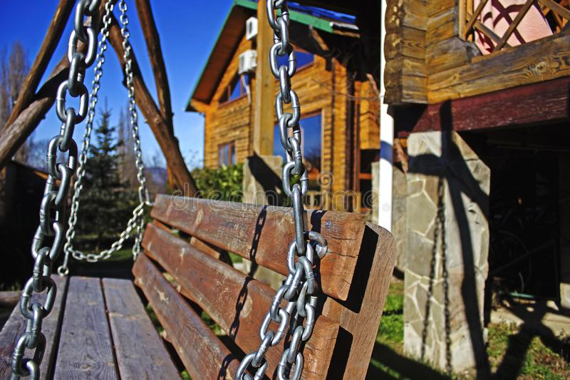 The element of the metal chain, as a decoration to the swings in the territory of the house for the rest. Metal chain on the street swing in the background of stock photo